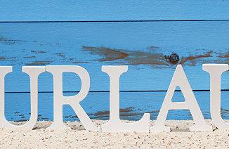 Das Wort Urlaub im Sand